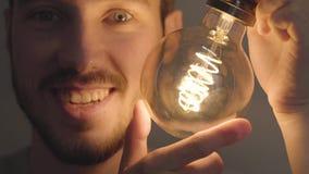Nahaufnahme der lächelnden bärtigen Mannschraube herein und heraus eine Glühlampe auf dem dunklen Hintergrund Konzept von hellem  stock footage