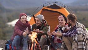 Nahaufnahme der lächelnden glücklichen Firma von vier jungen Freunden, die ein Picknick durch die Berge haben, plaudern sie und l stock video