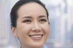 Nahaufnahme der lächelnden jungen Frau, die oben, Fokus auf Vordergrund schaut Stockbild