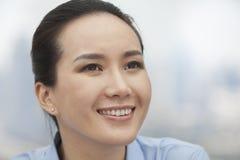 Nahaufnahme der lächelnden jungen Frau, die oben schaut Stockfotos