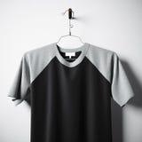 Nahaufnahme der leeren Baumwollt-shirt Schwarzfarbe, die in der leeren MittelBetonmauer hängt Klares Aufklebermodell mit in hohem Stockbild