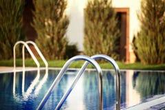 Nahaufnahme der Leiter im Swimmingpool Stockfotos