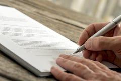 Nahaufnahme der männlichen Hand einen Vertrag oder ein Anmeldeformular unterzeichnend lizenzfreies stockbild