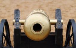 Nahaufnahme der Mündung der alten Metallkanone mit Rad auf Sand Stockfoto