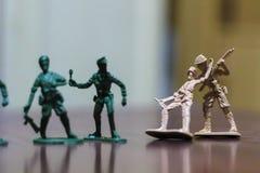 Nahaufnahme der Miniatur ein Gruppe Plastikspielwarensoldaten im Krieg Lizenzfreie Stockfotografie