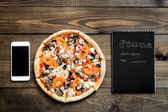Nahaufnahme der Pizza, des Handys und des Notizbuches mit dem Text: Pizzalieferung Hintergrundholztisch Notizbuchschwarzes Lizenzfreie Stockfotografie