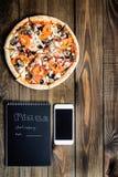 Nahaufnahme der Pizza, des Handys und des Notizbuches mit dem Text: Pizzalieferung Hintergrundholztisch Notizbuchschwarzes Lizenzfreie Stockfotos