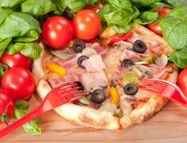 Nahaufnahme der Pizza mit roter Gabel, Tomaten, Käse und Basilikum auf hölzernem Hintergrund Stockbild