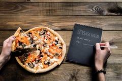 Nahaufnahme der Pizza und des Notizbuches mit dem Text: Pizzalieferung Hintergrundholztisch Notizbuchschwarzes mit weißem Text Stockbilder