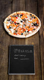 Nahaufnahme der Pizza und des Notizbuches mit dem Text: Pizzalieferung Hintergrundholztisch Notizbuchschwarzes mit weißem Text Lizenzfreie Stockfotos