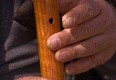 Nahaufnahme der rauen Arbeitskraft-Hände, die hölzerne Flöte spielen Lizenzfreie Stockbilder