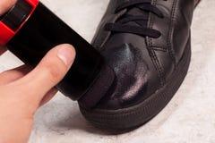 Nahaufnahme der Reinigungsschwarzschuhe mit schwarzer Paste Stockfotografie