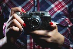 Nahaufnahme der Retro- Kamera in den Hippie-Mädchenhänden Stockfotografie
