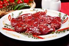 Nahaufnahme der rohen Rindfleischmedaillons mit Rosmarin, Pfeffer und Gewürzen Lizenzfreies Stockbild