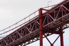 Nahaufnahme der roten Stahlträgerhängebrücke gegen grauen Himmel Lizenzfreie Stockbilder