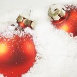 Nahaufnahme der roten Weihnachtskugeln im weißen Schnee Lizenzfreie Stockfotos