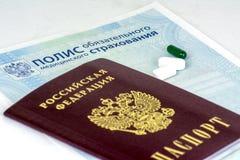 Nahaufnahme der russischen Krankenversicherungspolice und des russischen Passes und einiger Pillen stockfotos