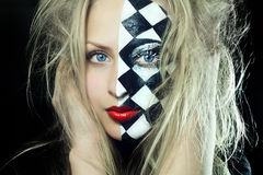 Nahaufnahme der Frau mit Schachmuster auf Gesicht Stockfotografie