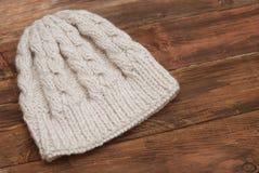 Nahaufnahme der schönen warmen Elfenbeinstrickmütze Gestrickter warmer handgemachter Hut mit schöner Verzierung auf hölzernem Hin stockfoto