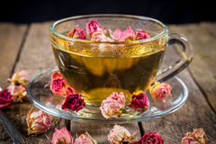 Nahaufnahme der Schale des grünen Tees mit den getrockneten rosafarbenen Knospen Lizenzfreie Stockfotos