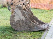 Nahaufnahme der schlammigen Baggerschaufel auf Gras nahe Bau sind Lizenzfreies Stockfoto