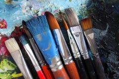 Nahaufnahme der schmutzigen Pinsel auf Palette Lizenzfreie Stockfotos