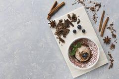 Nahaufnahme der SchokoladenEiscreme mit Blaubeeren, Schokolade und Zimt auf einem grauen Hintergrund Lizenzfreie Stockbilder