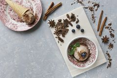 Nahaufnahme der SchokoladenEiscreme mit Blaubeeren, Schokolade und Zimt auf einem grauen Hintergrund Stockbild