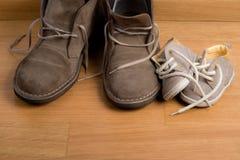 Nahaufnahme der Schuhe des Vaters nah an den Schuhen des Kindes Stockfotos