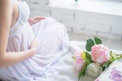Nahaufnahme der schwangeren Frau im netten weißen Kleid, das ihren Bauch mit den Händen berührt und einen Blumenstrauß von Pfings lizenzfreie stockfotografie