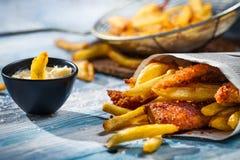 Nahaufnahme der selbst gemachten Fische u. der Chips und der Soße Stockbilder