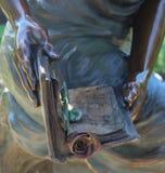 Nahaufnahme der Statue übergibt das Halten des Buches bookmarkt mit einer Rose Lizenzfreies Stockfoto