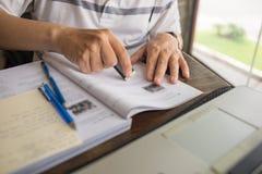 Nahaufnahme der Studentenhand unter Verwendung des Radiergummis auf Arbeitsbuch beim Studieren stockbild