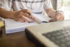 Nahaufnahme der Studentenhand unter Verwendung des Stiftes beim Studieren auf Arbeitsbuch stockfotografie