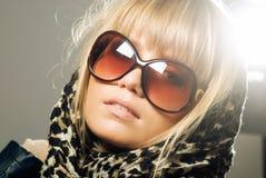 Nahaufnahme der tragenden Sonnenbrille einer jungen Frau und des Schals Stockfotografie