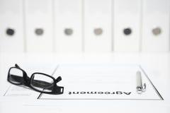Nahaufnahme der Vereinbarung, der Gläser und des Stiftes mit Mappen in unscharfem Ba Lizenzfreie Stockbilder