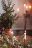 Nahaufnahme der weißen brennenden Kerze auf dem Hintergrund von Fichtenzweigen Dekor des neuen Jahres und des Weihnachten Stockbilder