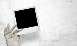 Nahaufnahme der weißen hölzernen Hand mit polaroidrahmen Stockfotos