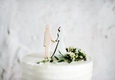 Nahaufnahme der weißen Hochzeitstorte mit Braut und Bräutigam Figure Toppe Stockfoto