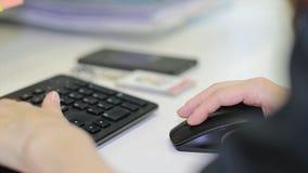 Nahaufnahme der weiblichen Hand auf schwarzer Maus Frau ` s Hand unter Verwendung der drahtlosen Maus auf weißer Tabelle Schließe stockbild
