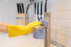 Nahaufnahme der weiblichen Hand in den Handschuhen, die den Küchenhahn säubern Lizenzfreies Stockbild