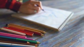 Nahaufnahme der weiblichen Handmalereiskizze auf Papiernotizbuch mit Bleistiften Künstlerin bei der Arbeit Lizenzfreies Stockfoto