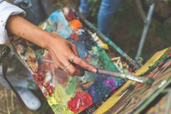 Nahaufnahme der weiblichen Künstlerhandfarbe ein Bild auf einer Palette an der Werkstatt, Abschluss herauf Draufsicht Stockfotografie