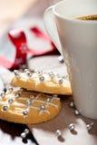 Nahaufnahme der Weihnachtsbiskuite und des Bechers Kaffees Stockfotografie