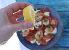 Nahaufnahme der Zitrone, die auf Salat zusammengedrückt wird stockbild