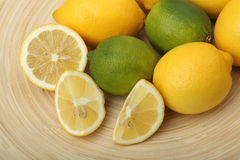 Nahaufnahme der Zitronen und der Kalke auf einer hölzernen Platte auf grünem Hintergrund Stockfoto