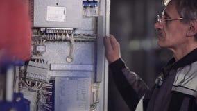 Nahaufnahme des älteren öffnenden Stromzählers des Arbeiters stock video