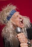 Nahaufnahme des älteren männlichen Sängers, der über Rot singt, färbte Hintergrund Stockfotografie