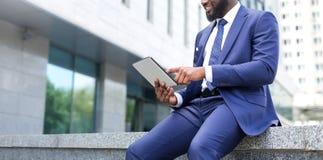 Nahaufnahme des afrikanischen Geschäftsmannes, der eine digitale Tablette beim Sitzen der Bürovoraussetzungen verwendet lizenzfreies stockbild