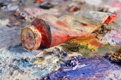 Nahaufnahme des alten Ölfarberohrs mit der roten Farbe, die auf Palette liegt Stockbilder